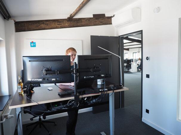 e-pixler Entwicklerin am höhenverstellbaren Schreibtisch
