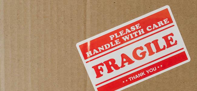 Umzugskarton mit Aufkleber auf dem steht: Please handle with care, Fragil